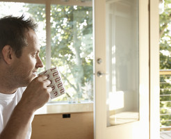 Man sitting indoors, drinking cup of coffee, side view